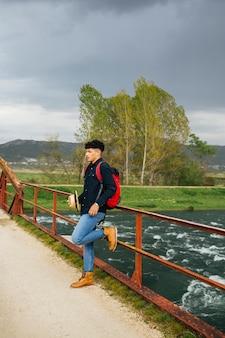 Stylish man holding hat leaning on bridge railing over flowing river