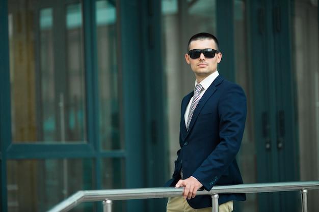 건물의 배경에 양복과 안경에 세련된 남자