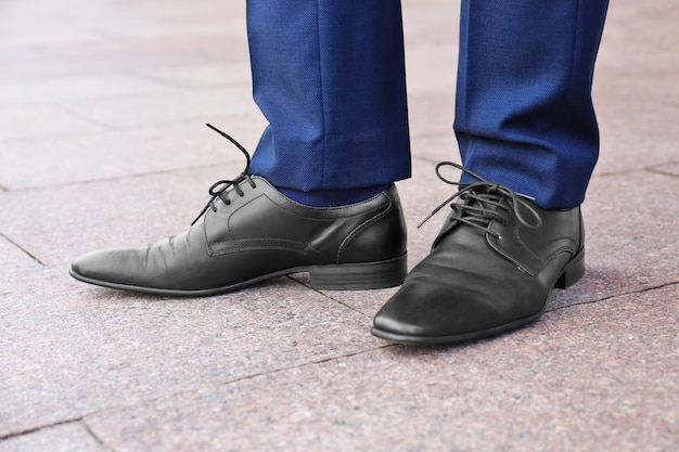 야외에서 검은 가죽 신발에 세련 된 남자