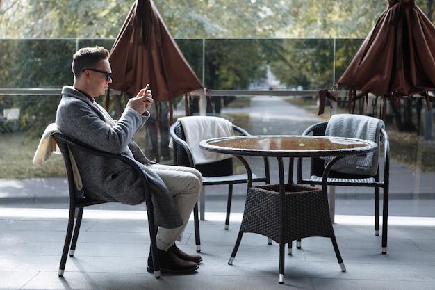 黒のサングラスとコートを着たスタイリッシュな男性が、カフェのテーブルでスマートフォンでコミュニケーションを取ります。