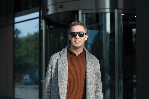 黒のサングラスと屋外のコートを着たスタイリッシュな男。