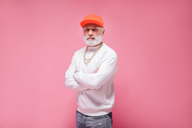 ピンクの壁に帽子と白いセーターのポーズでスタイリッシュな男