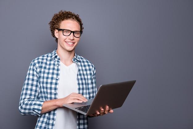 Стильный мужчина в случайных клетчатых очках рубашки держит набор текста нетбука