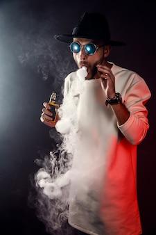 Стильный мужчина в солнцезащитных очках, надувает пар на черном