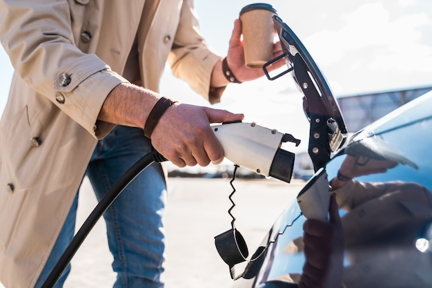 Stylish man inserts plug of the charger into the socket of electric car closeup