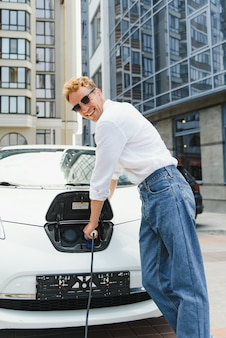 세련된 남자는 충전기의 플러그를 전기 자동차 클로즈업 소켓에 삽입합니다.