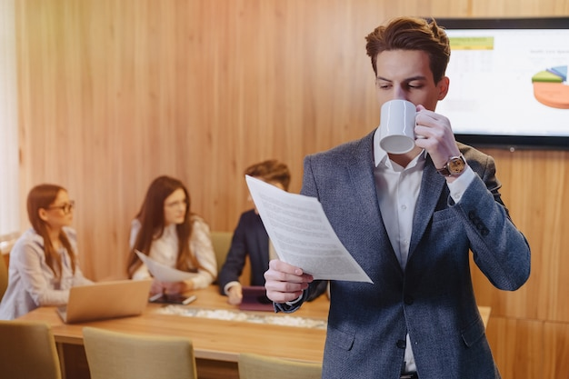 A stylish man in a jacket and a shirt with a cup of coffee in his hand stands and reads documents