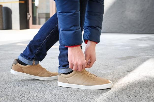 街の通りにベージュの靴をひもで締めるスタイリッシュな男