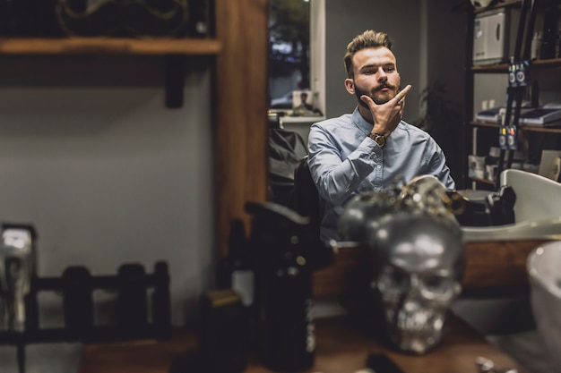 Stylish man looking at reflection in barbershop