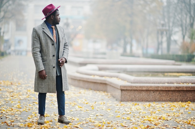 Stylish man model in gray coat, jacket tie and red hat posed at foggy weather street