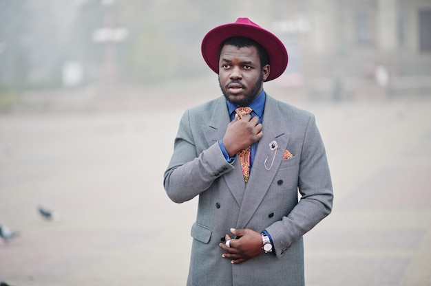 Stylish man model in gray jacket tie and red hat posed on street with fog