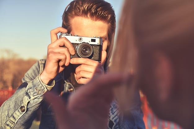 通りのレトロなカメラで女性を撮影するスタイリッシュな男性