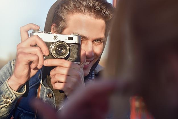 通りのレトロなカメラで女性を撮影するスタイリッシュな男性。