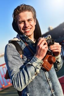 レトロなカメラで撮影するスタイリッシュな男。観光客は橋の上に滞在して写真を撮ります。