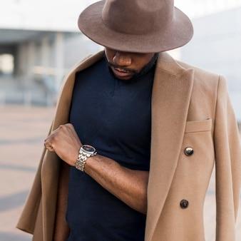 Uomo alla moda che posa in un modo misterioso mentre guarda il suo orologio