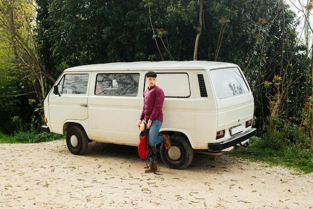 Stylish man posing near white van with holding backpack