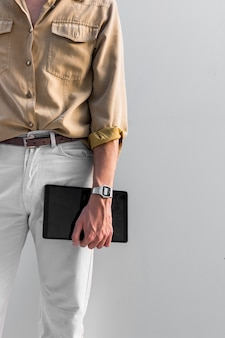 Stylish man posing outdoors while holding tablet