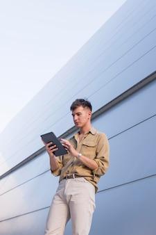 Стильный мужчина позирует на открытом воздухе, глядя на планшет