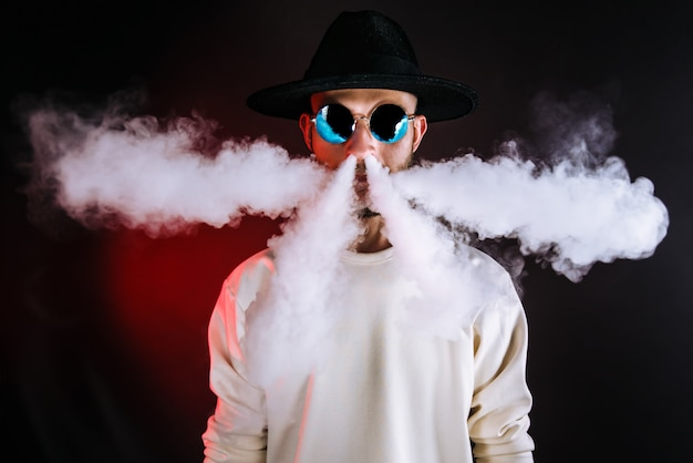 Stylish man puffing vapor