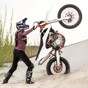 Stylish man raising motorbike in the desert