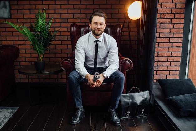Uomo alla moda che legge il giornale di affari e che si siede sul divano.