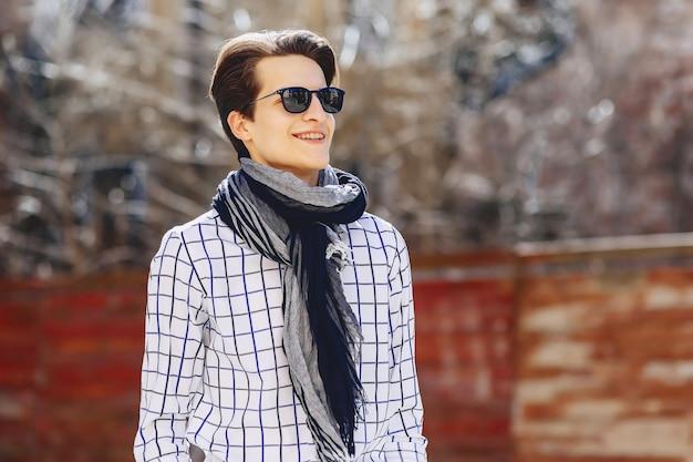 Stylish man in shirt and sunglasses on suuny urban street