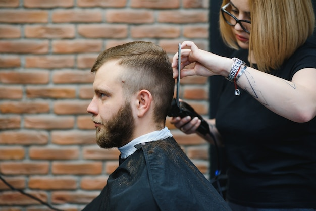 理髪店に座っているスタイリッシュな男性ヘアスタイリスト美容師髪を切る女性
