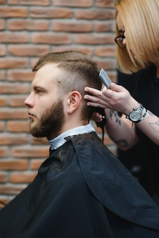 Stylish man sitting barber shop hairstylist hairdresser woman cutting his hair
