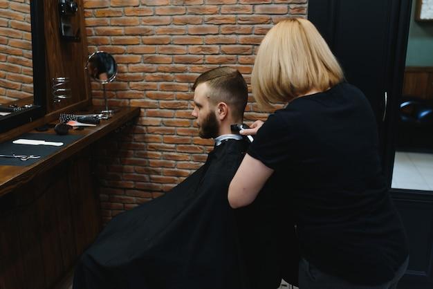 理髪店に座っているスタイリッシュな男性ヘアスタイリスト美容師