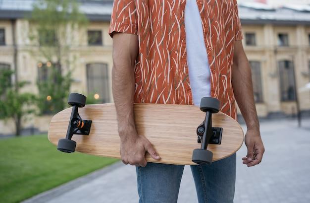 Стильный конькобежец держит longboard, стоя на улице