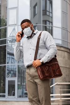 Uomo alla moda che parla al telefono con la maschera mentre si recava al lavoro durante la pandemia