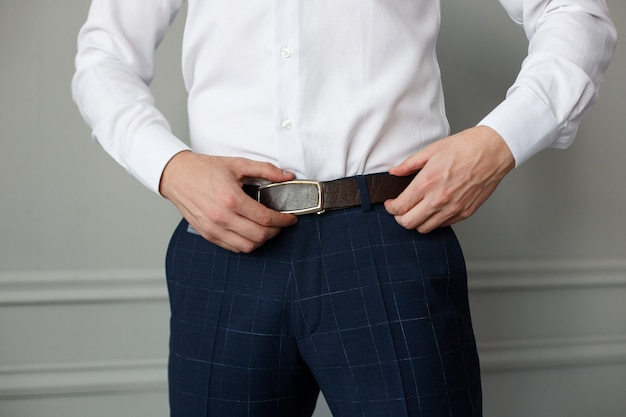 Stylish man in  trousers and a white shirt fastened a brown leather belt. men's formal outfit close up. handsome guy puts on suit