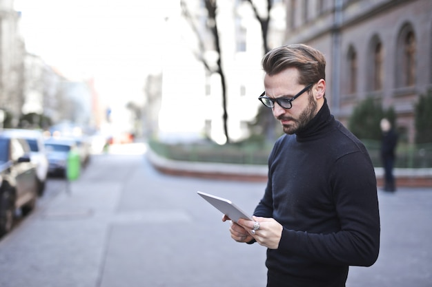 Stylish man using a tablet on the street