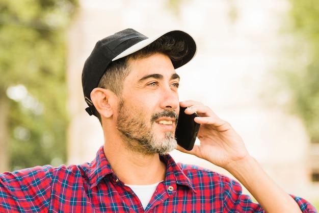 Stylish man wearing black cap on his head talking on mobile phone