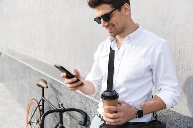 Стильный мужчина в солнечных очках, пьёт кофе на вынос и пользуется мобильным телефоном, стоя с велосипедом вдоль стены на открытом воздухе