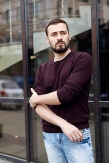 가죽 코트를 입고 거리에 서 있는 수염을 기른 세련된 남자. 거리에서 남자를 촬영합니다. 세련된 스타일의 남자. 우아한 남자의 헤어 스타일
