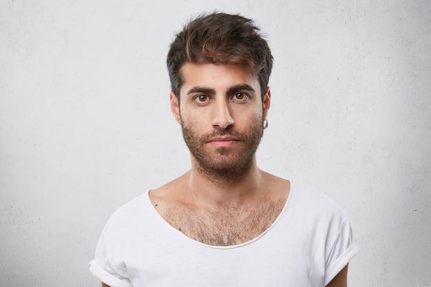 Стильный мужчина с бородой, модной прической, с серьгой в ухе и белой футболкой смотрит прямо своими темными глазами