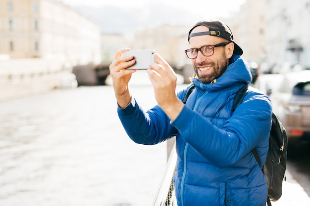 Stylish man with blue charming eyes and beard wearing blue anorak, eyewear and cap making selfie with mobile phone