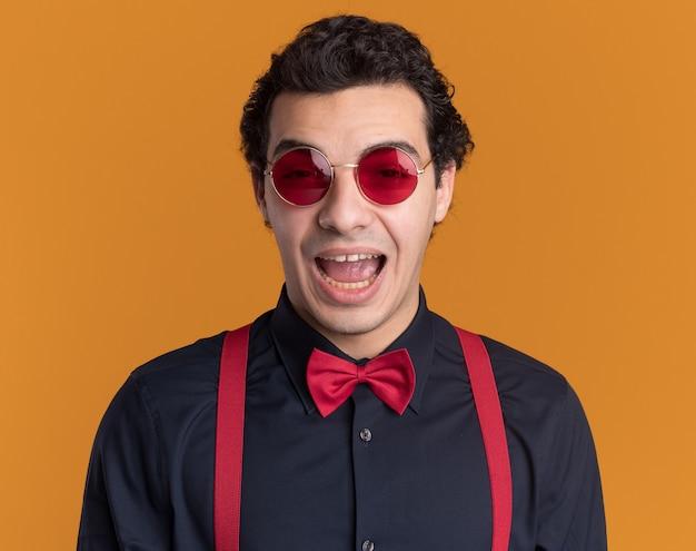 オレンジ色の壁の上に立っている正面を見て幸せで興奮して眼鏡とサスペンダーを身に着けている蝶ネクタイを持つスタイリッシュな男