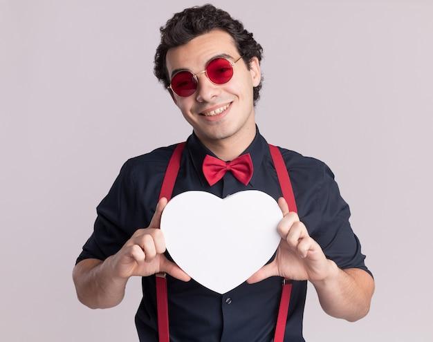 흰 벽 위에 유쾌하게 서있는 정면을보고 골판지 심장을 들고 안경과 멜빵을 착용하는 나비 넥타이와 세련된 남자