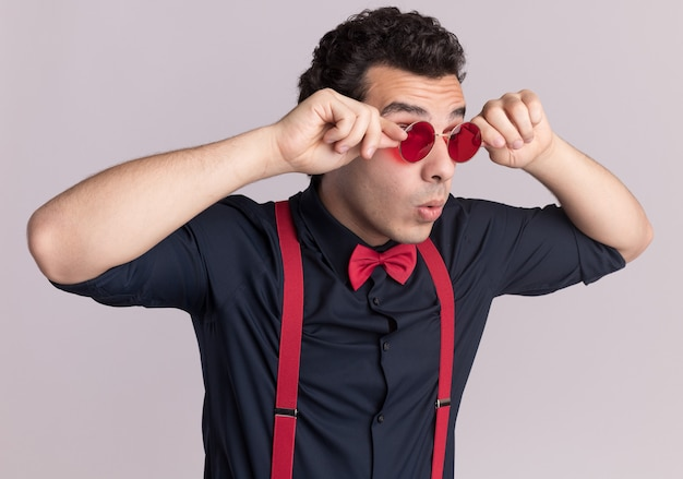 眼鏡とサスペンダーを身に着けている蝶ネクタイを身に着けているスタイリッシュな男は、白い壁の上に立っている彼の眼鏡を固定して驚いた