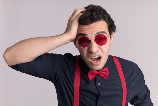 흰 벽 위에 서있는 실수로 그의 머리에 손으로 혼란스러워하는 안경과 멜빵을 착용하는 나비 넥타이와 세련된 남자