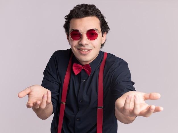 Стильный мужчина с бабочкой в очках и подтяжках смотрит вперед, протягивая руки, как спрашивает, улыбаясь, стоя над белой стеной