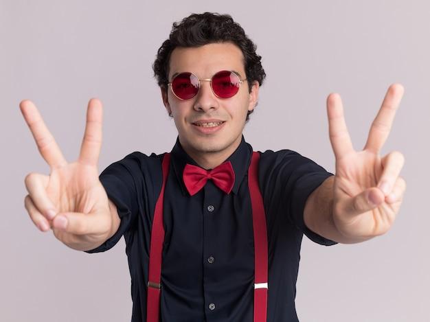 안경과 멜빵을 착용하는 나비 넥타이와 세련된 남자가 흰 벽 위에 서있는 v 기호를 보여주는 얼굴에 미소로 정면을보고