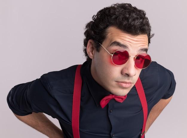 안경과 멜빵을 착용하는 나비 넥타이와 세련된 남자