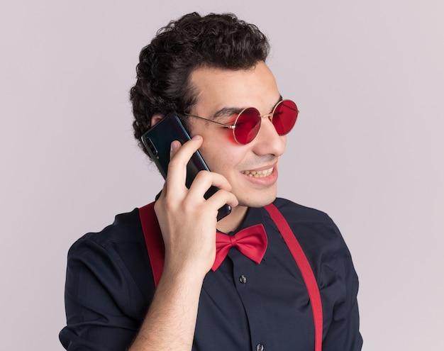 안경과 멜빵을 착용하는 나비 넥타이와 세련된 남자가 흰 벽 위에 서있는 휴대 전화로 이야기 웃고