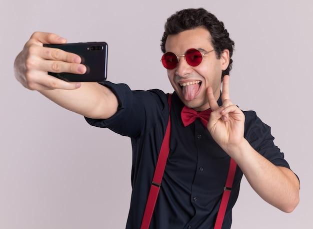 흰색 벽 위에 유쾌하게 서있는 혀를 튀어 나와 v 기호를 보여주는 셀카를 보여주는 스마트 폰을 사용하여 안경과 멜빵을 착용하는 나비 넥타이와 세련된 남자
