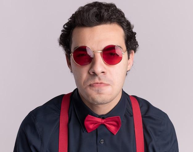 Uomo alla moda con il farfallino con gli occhiali e le bretelle guardando la parte anteriore dispiaciuta che increspa le labbra in piedi sul muro bianco