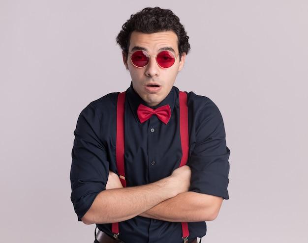Uomo alla moda con farfallino che indossa occhiali e bretelle guardando davanti annoiato e molto ansioso con le braccia incrociate in piedi sopra il muro bianco