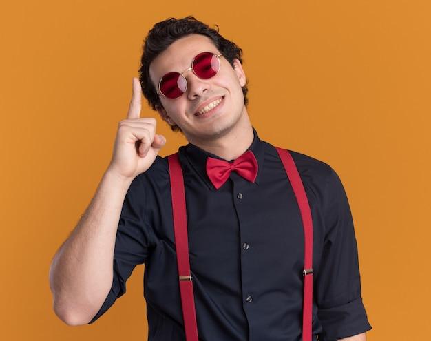 Uomo alla moda con il farfallino con gli occhiali e le bretelle guardando il dito indice che mostra felice e positivo davanti sorridendo allegramente in piedi sopra la parete arancione
